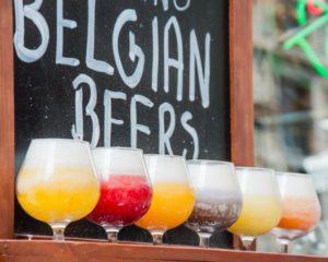 Gläser mit verschiedenfarbigen belgischen Bieren vor Kreidetafel
