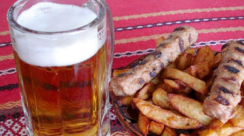 Bierkrug mit hellem, schäumendem bulgarischem Bier, danaben Teller mit Imbiss
