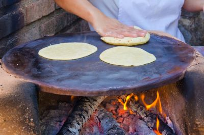 Offenes Feuer mit Metallplatte, auf der Tortillas gebacken werden.