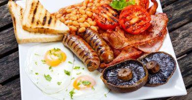 Teller mit englischem Frühstück: Bacon, Spiegelei, Würstchen, Tomaten, Champignons, Bakes Beans und Toast