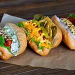 Drei verschiedene Hot Dogs auf Holztisch