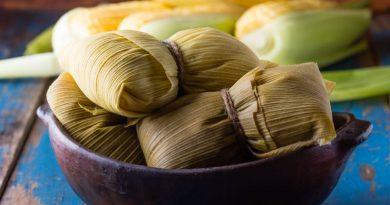 Schale mit mehreren Humitas, im Hintergrund die Maiskolben