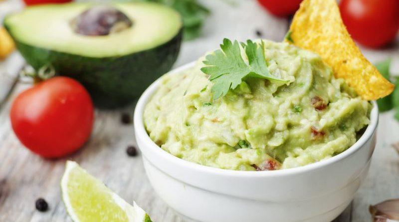 Schalte frischer Guacamole auf Tisch mit Avocado, Limettenstück und Tomaten
