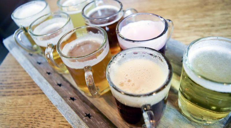 7 Glaskrüge mit verschiedenen belgischen Bieren auf Holztablett