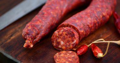 Chorizo Wurst auf Holzbrett mit einigen roten Paprika