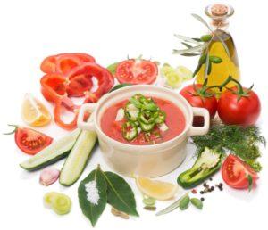 Schale Gazpacho, darum die Zutaten Tomaten, Gurken, Paprika, Öl und Kräuter.