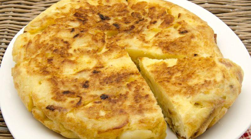 Tortilla de patatas , ein Stück heraus geschnitten