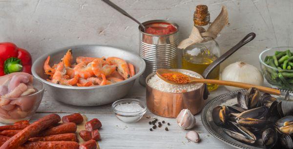 Tisch mit Zutaten für Paella: Reis, Fisch, Fleisch und mehr