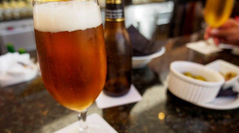 Glas mit spanischem Bier, im Hintergrund Flasche und Schale Oliven