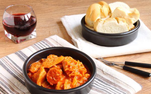 Tisch mit Schalte Callos a la madrileña, Schalte mit Weißbrot und Glas Rotwein