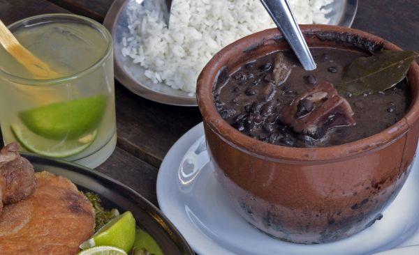 Tisch mit Schale Feijoada, Schale Reis und Glas Caipirinha