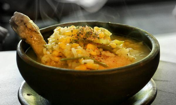 Cazuela de Ave in dunkler Schale, zu sehen ist auch Reis und gebratenes Hühnchen