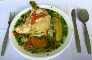 Teller Cazuela de Ave mit großem Stück Hühnchen und Besteck am Tisch