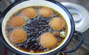 Halbfertige Acarajé schwimmen zum frittieren im Fett in einem Topf