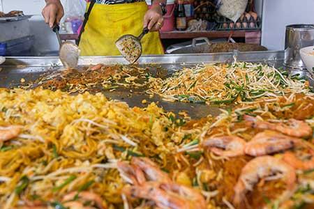 Große Bratfläche mit Zutaten zu Pat Thai in der Zubereitung