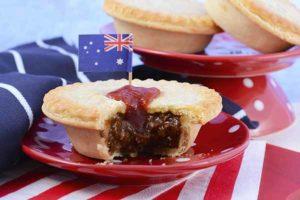 Australischer Meat Pie mit australischer Flagge auf rotem Teller.