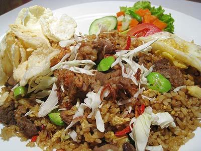 Teller Nasi Goreng Kambing (mit Ziegenfleisch) und Petai (gründe Bohnen).