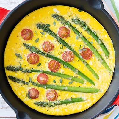 Spanne von oben mit Frittata Aperagi, zu sehen ist die gelbe Masse, mehrere grüne Spargel und rote halbe Tomaten.