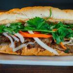 Bánh mì belegt von vorne: gut zu sehen Korianderblätter, eingelegte Karotten und Rettich.