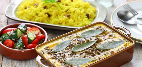 Tisch mit Bobotie in Auflaufform, eine Platte gelber Reis und Tomaten-Gurken-Salat.